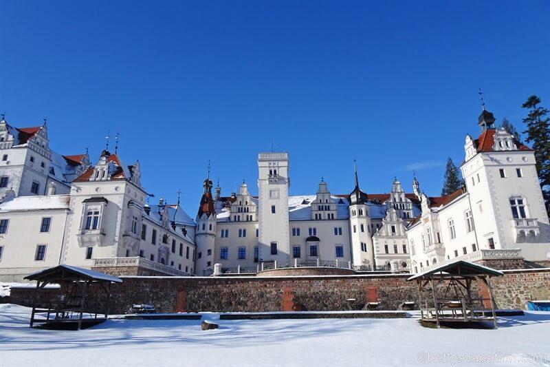Weißes Renaissanceschloss vor blauem Himmel und von Schnee umgeben.